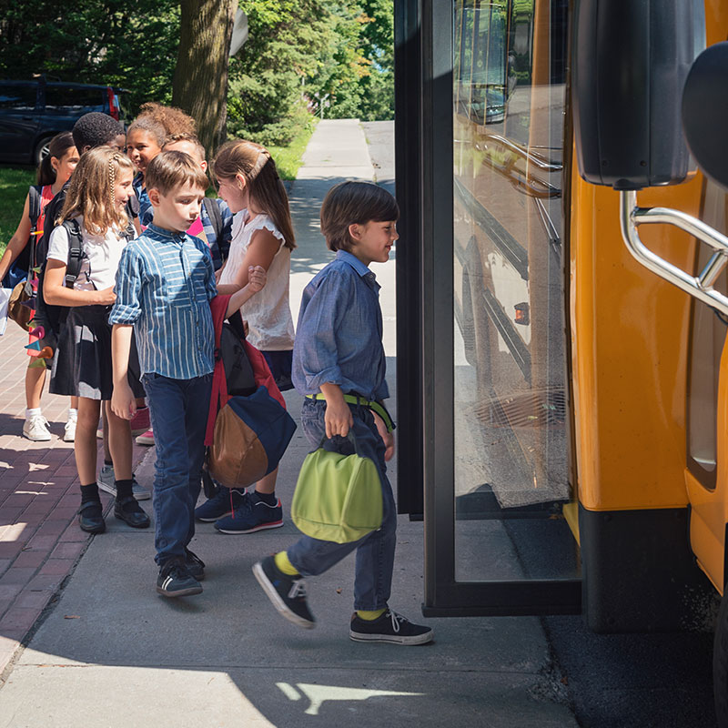 A group of children boarding a yellow school bus